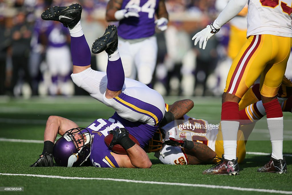Rhett Ellison of the Minnesota Vikings is tackled by Perry Riley of the Washington Redskins during the third quarter on November 2 2014 at TCF Bank...