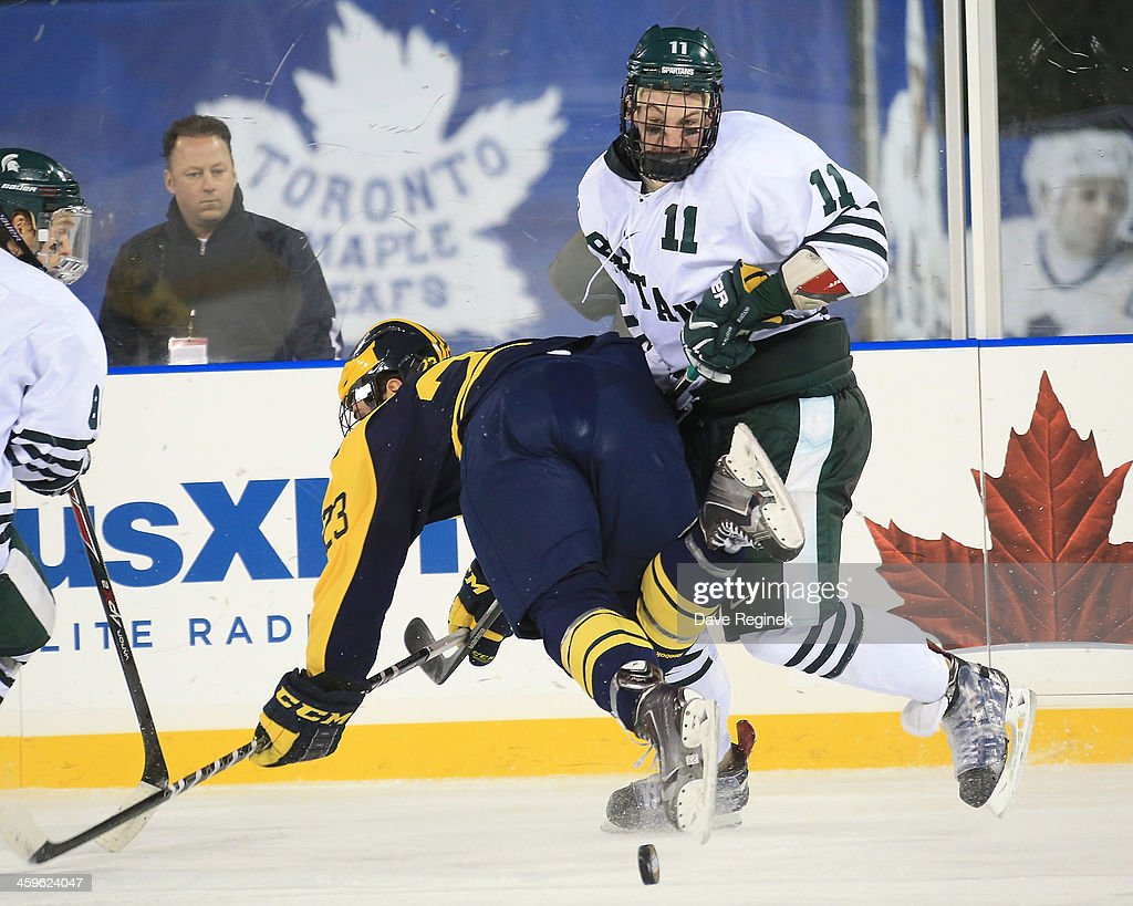 Rhett Holland #11 of the Michigan State Spartans collides with Alex Kile #23 of the University of Michigan Wolverines during the consolation game of the Hockeytown Winter Festival Great Lakes Invitational - Day 2 played outdoors at Comerica Park on December 28, 2013 in Detroit, Michigan. The Spartans won 3-0