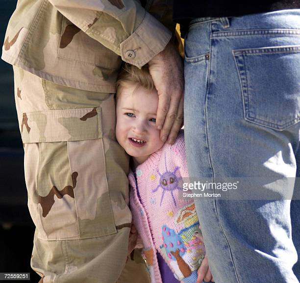 Rhiannon Taylor fouryearsold gets squeezed between her father Gunnery Sgt Greg Taylor and her mother Lyla while they kiss goodbye at Marine Corp Air...