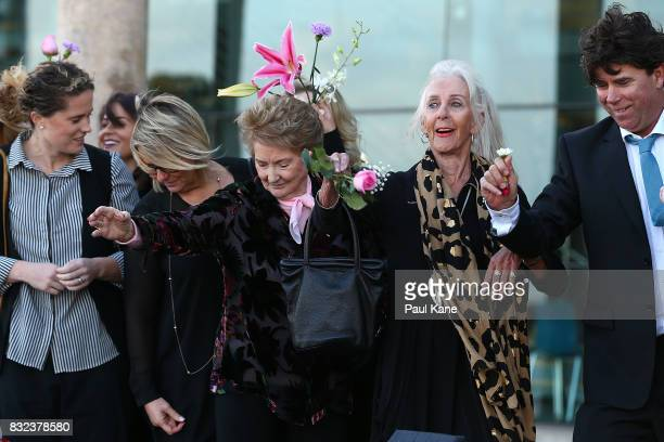 Rhonda Gillam and Marie Johnston throw flowers into the esturay following the funeral service for Betty Cuthbert at Mandurah Performing Arts Centre...