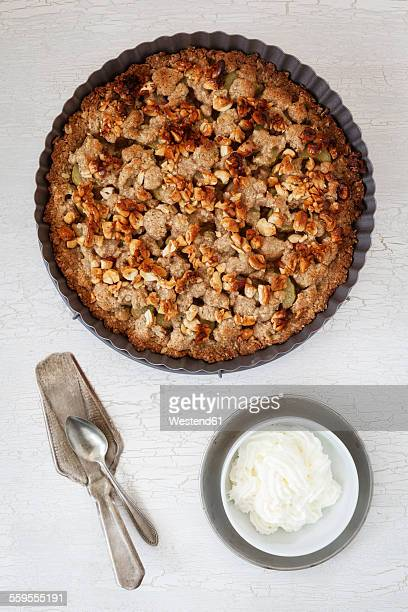 Rhubarb crumble cake in a baking dish and bowl of whipped cream