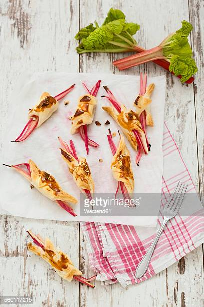 Rhubarb in puff pastry with almond slivers on paper and kitchen towel