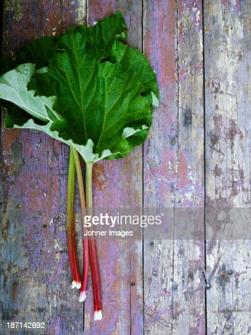 Rhubarb leaves on wooden surface, directly above