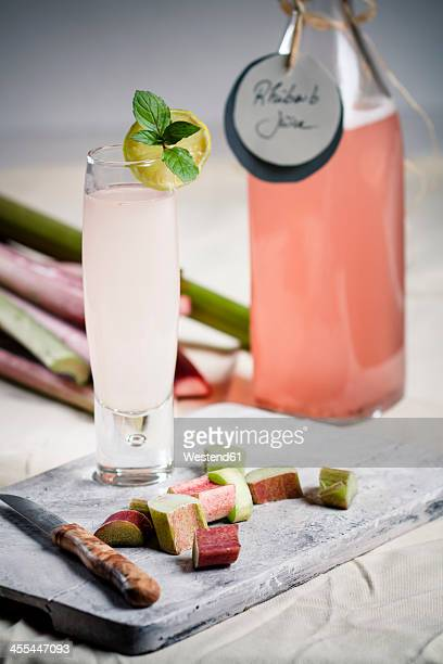 Rhubarb pieces with knife and glass of rhubarb juice on chopping board, close up