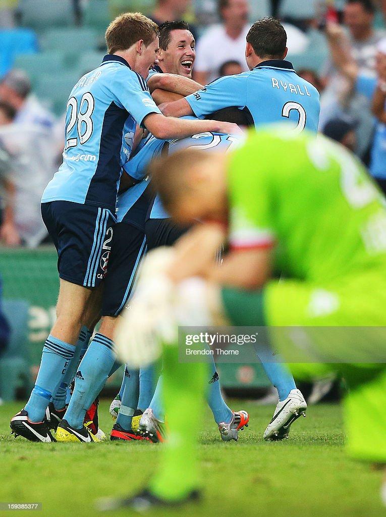 Rhyan Grant of Sydney is hugged by team mates after scoring the winning goal in extra time as Andrew Redmayne of the Heart slumps to one knee during the round 16 A-League match between Sydney FC and the Melbourne Heart at Allianz Stadium on January 13, 2013 in Sydney, Australia.