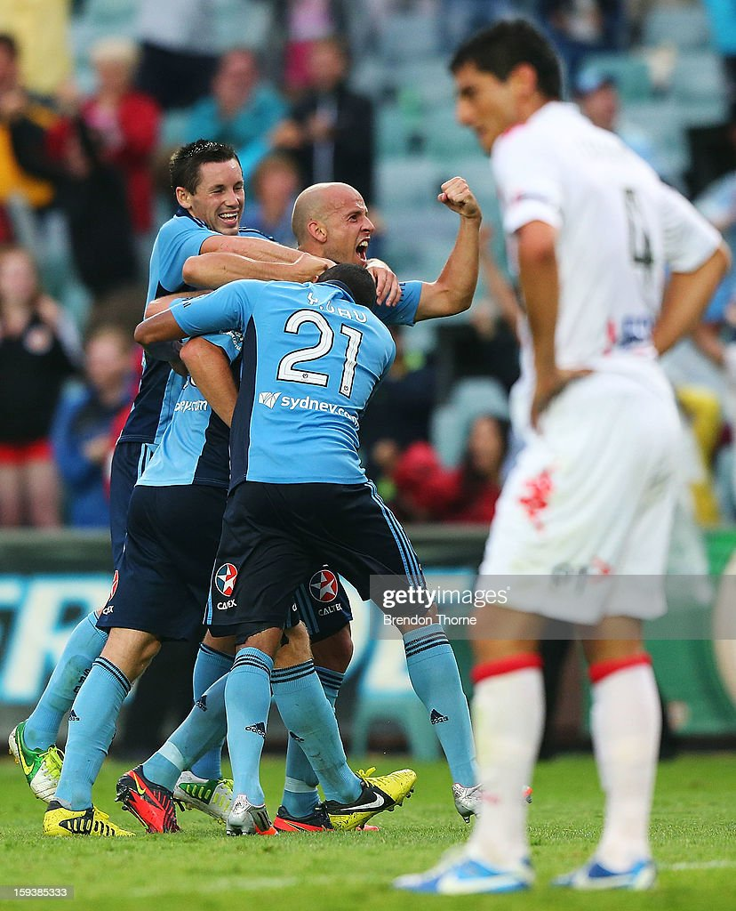 Rhyan Grant of Sydney is hugged by team mates Blake Powell, Yairo Yau and Trent McClenahan after scoring the winning goal in extra time during the round 16 A-League match between Sydney FC and the Melbourne Heart at Allianz Stadium on January 13, 2013 in Sydney, Australia.