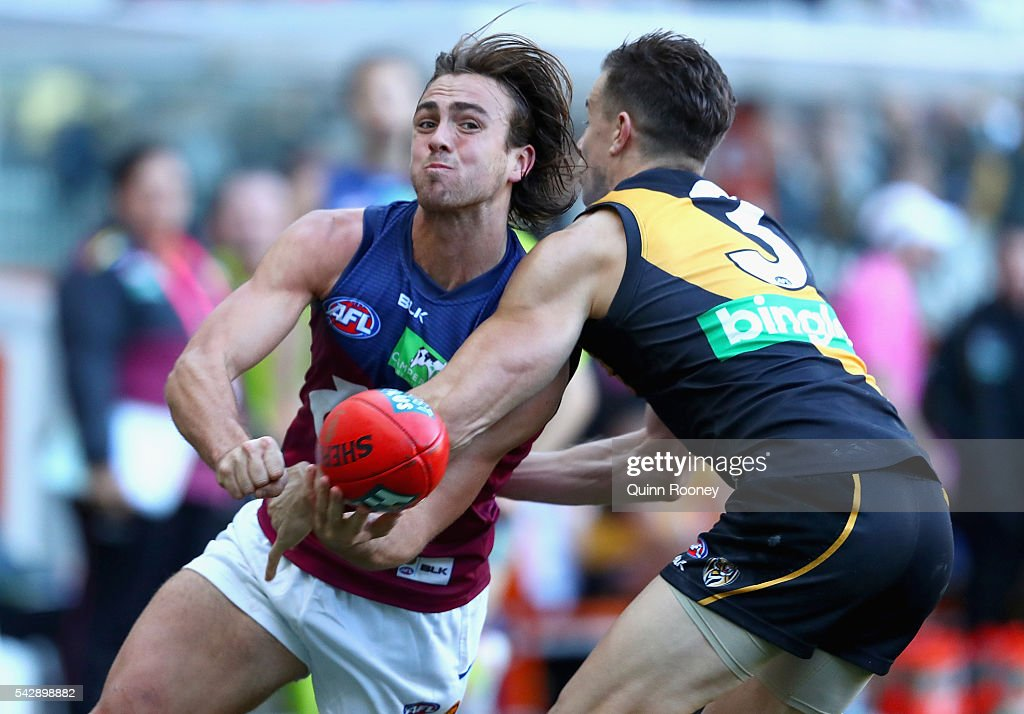 Rhys Mathieson of the Lions handballs whilst being tackled by <a gi-track='captionPersonalityLinkClicked' href=/galleries/search?phrase=Brett+Deledio&family=editorial&specificpeople=524933 ng-click='$event.stopPropagation()'>Brett Deledio</a> of the Tigers during the round 14 AFL match between the Richmond Tigers and the Brisbane Lions at Melbourne Cricket Ground on June 25, 2016 in Melbourne, Australia.
