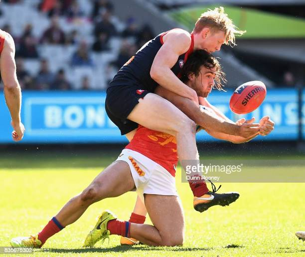 Rhys Mathieson of the Lions handballs whilst being tackled by Clayton Oliver of the Demons during the round 22 AFL match between the Melbourne Demons...