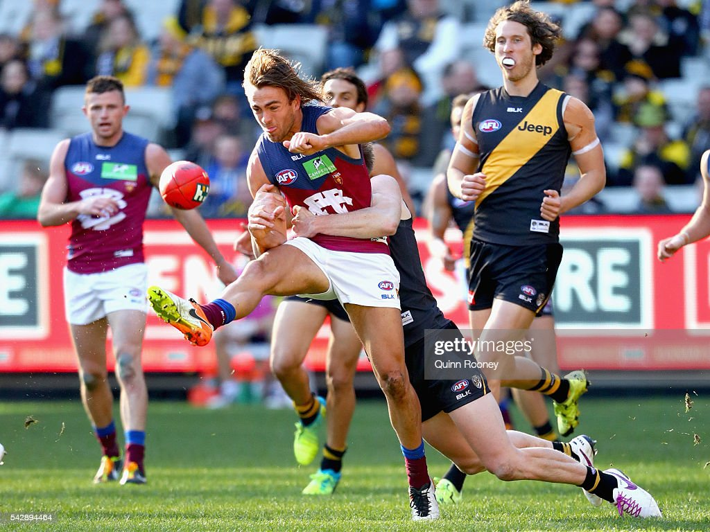 Rhys Mathieson of the Lions kicks whilst being tackled by <a gi-track='captionPersonalityLinkClicked' href=/galleries/search?phrase=Jack+Riewoldt&family=editorial&specificpeople=2327975 ng-click='$event.stopPropagation()'>Jack Riewoldt</a> of the Tigers during the round 14 AFL match between the Richmond Tigers and the Brisbane Lions at Melbourne Cricket Ground on June 25, 2016 in Melbourne, Australia.