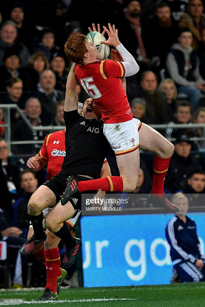 Rhys Patchell of Wales (top) jumps for the ball with New Zealand's Ben Smith during the third rugby union Test match between the New Zealand All Blacks and Wales at Forsyth Barr Stadium in Dunedin on June 25, 2016. / AFP / Marty Melville
