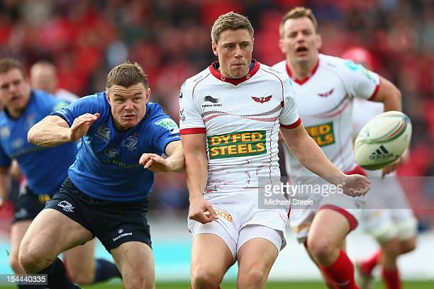 Rhys Priestland of Scarlets feeds a pass as Brian O'Driscoll of Leinster closes in during the Heineken Cup Pool 5 match between Scarlets and Leinster...