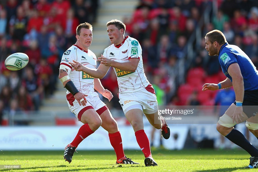 <a gi-track='captionPersonalityLinkClicked' href=/galleries/search?phrase=Rhys+Priestland&family=editorial&specificpeople=4195648 ng-click='$event.stopPropagation()'>Rhys Priestland</a> (C) of Scarlets feeds a pass during the Heineken Cup Pool 5 match between Scarlets and Leinster at Parc y Scarlets on October 20, 2012 in Llanelli, Wales.