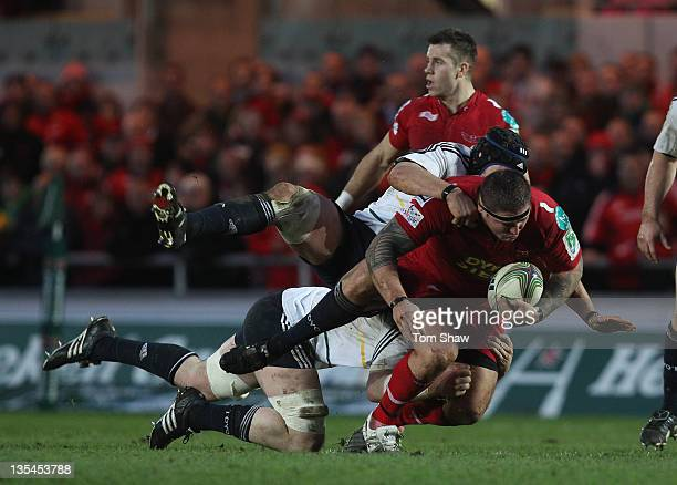 Rhys Thomas of Scarlets is tackled during the Heineken Cup match between Scarlets and Munster at Parc y Scarlets on December 10 2011 in Llanelli Wales