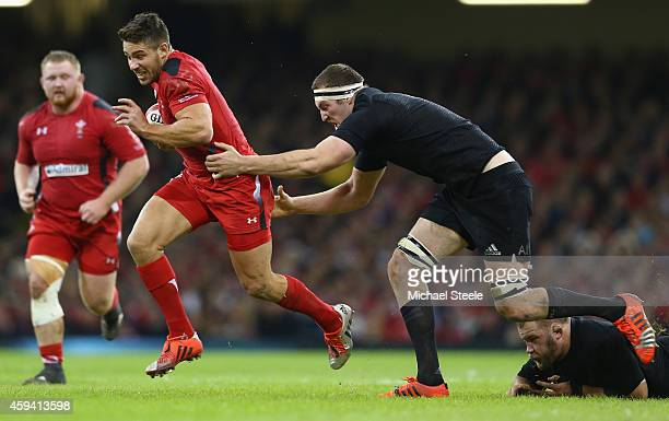 Rhys Webb of Wales bursts past the challenge of Brodie Retallick of the All Blacks during the International match between Wales and New Zealand at...