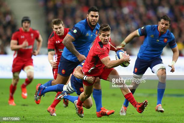 Rhys Webb of Wales pulls away from the challenge of Sebastien TillousBorde of France to set up his sides first try scored by Dan Biggar during the...