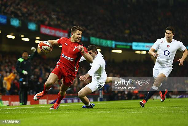 Rhys Webb of Wales skips a tackle from Jonny May of England as he goes over to score the opening try during the RBS Six Nations match between Wales...