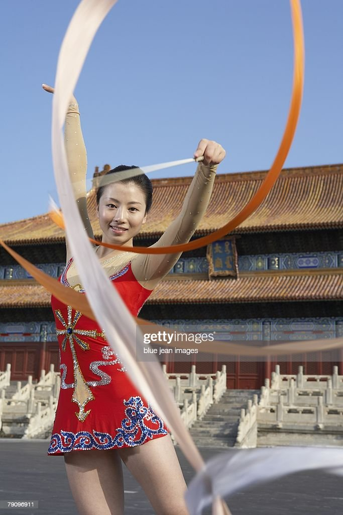 A rhythmic gymnastics athlete practices in front of an ancient, Ming Dynasty-style Chinese temple square, early morning. : Stock Photo