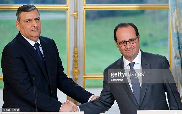 Riad Hijab chief coordinator of the Syrian opposition's High Negotiations Committee shakes hand with French President Francois Hollande after a press...