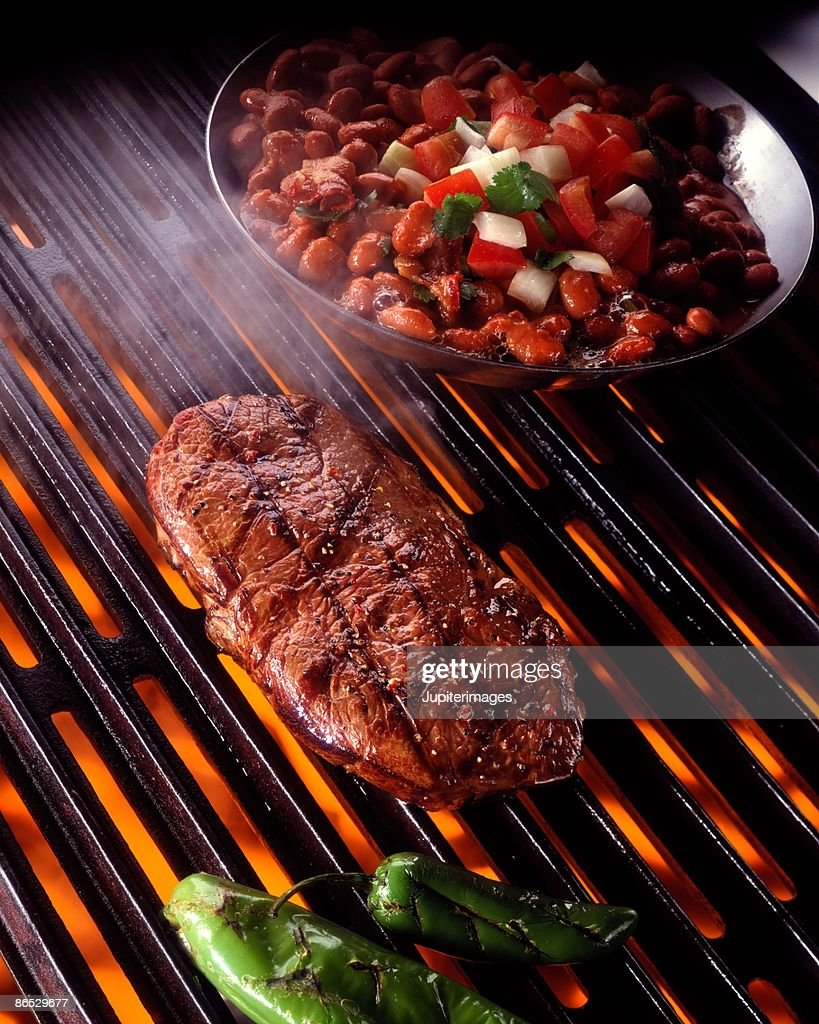 Rib eye steak on grill with beans : Stock Photo