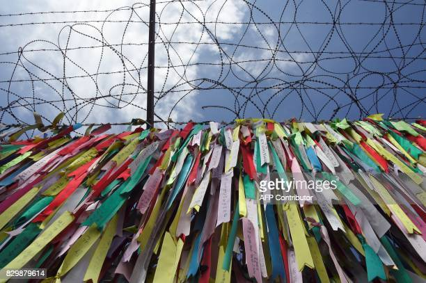 TOPSHOT Ribbons with inscriptions calling for peace and reunification are displayed on a military fence at Imjingak peace park near the Demilitarized...