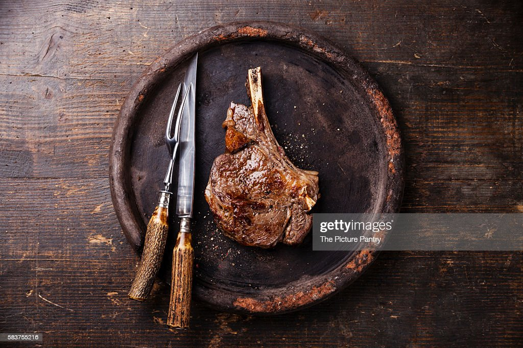 Ribeye Steak on bone and fork and knife carving set on stone plate on wooden background