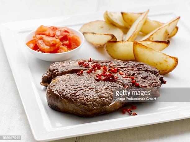 Ribeye steak with baked potato wedges