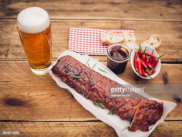 Ribs with sauce, chillies and a tall glass of beer