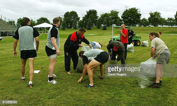 Ric Suggitt the Canadian Coach holds a plastic bag as his players clear the pitch of grass cuttings during the Canadian Rugby Union training held at...