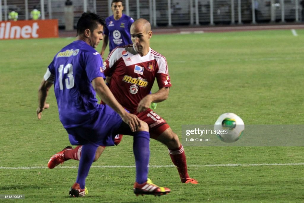 Ricardo Andreutti of Caracas FC competes for the ball with Vargas Lucena of Deportivo La Guaira during a match between Caracas FC and Deportivo La Guaira as part of the Apertura 2013 at Brígido Iriarte Stadium on September 25, 2013 in Caracas, Venezuela.