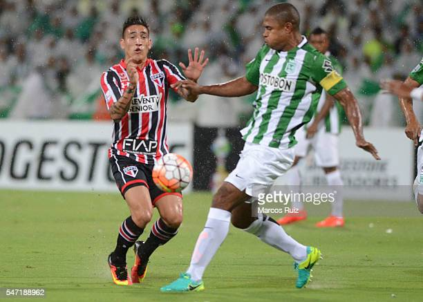 Ricardo Centurion of Sao Paulo fighs for the ball with Alexis Henriquez of Atletico Nacional during a second leg semi final match between Atletico...