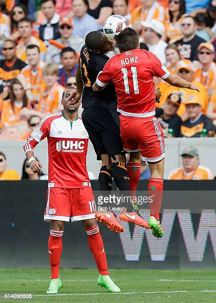 Ricardo Clark of Houston Dynamo and Kelyn Rowe of New England Revolution go up for a header as Teal Bunbury looks on at BBVA Compass Stadium on March...