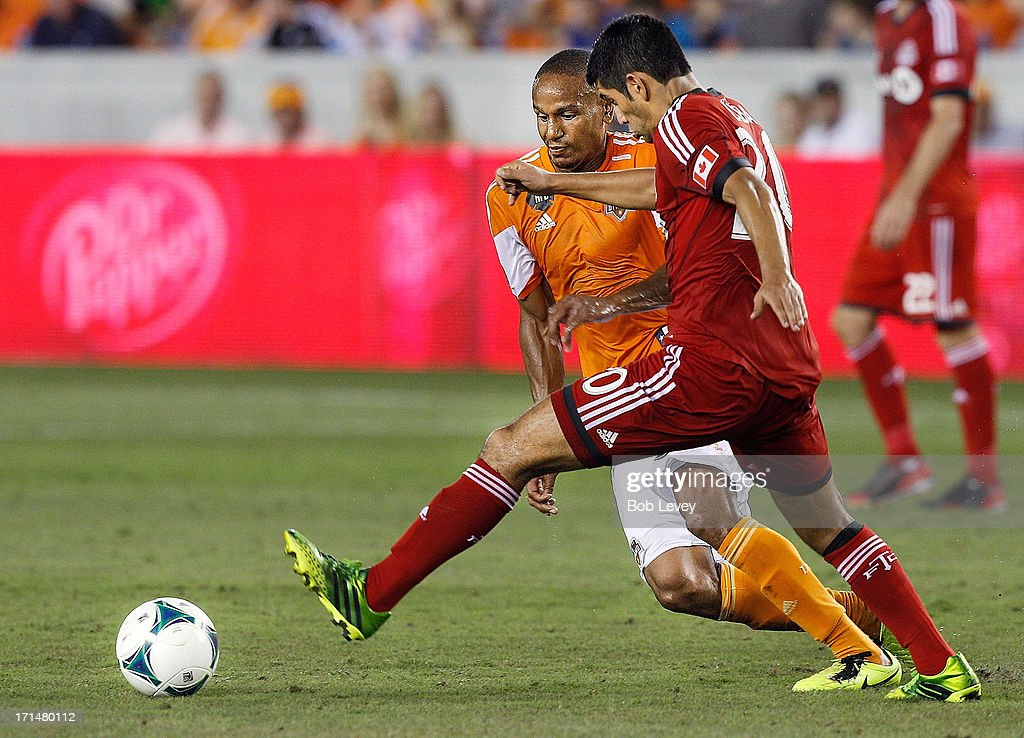 Ricardo Clark #13 of Houston Dynamo and Matias Laba #20 of Toronto FC during the game action at BBVA Compass Stadium on June 22, 2013 in Houston, Texas.