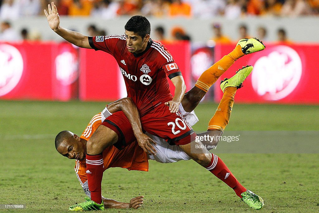 Ricardo Clark #13 of Houston Dynamo and Matias Laba #20 of Toronto FC get tangled up fighting for possesion of the ball in the second half at BBVA Compass Stadium on June 22, 2013 in Houston, Texas.