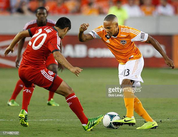 Ricardo Clark of Houston Dynamo attempts to get around Matias Laba ofToronto FC at BBVA Compass Stadium on June 22 2013 in Houston Texas