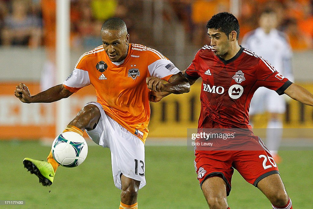 Ricardo Clark #13 of Houston Dynamo gets control of the ball as he is defended by Matias Laba #20 of Toronto FC at BBVA Compass Stadium on June 22, 2013 in Houston, Texas.