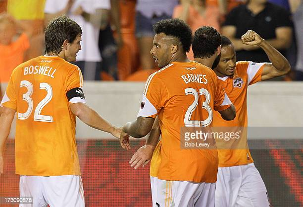 Ricardo Clark of the Houston Dynamo celebrates with teammates Giles Barnes and Adam Moffat and Bobby Boswell after his secondhalf goal against the...