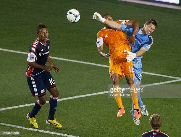 Ricardo Clark of the Houston Dynamo leaps for a ball against keeper Bobby Shuttleworth of the New England Revolution in the second half at BBVA...