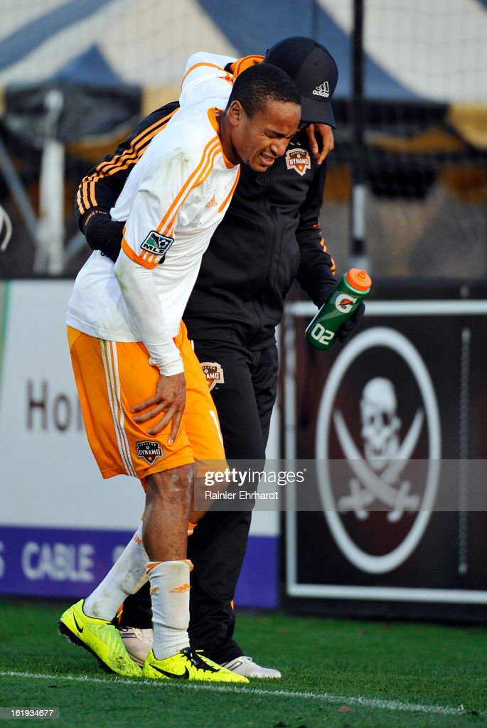 Ricardo Clarke #13 of the Houston Dynamo is helped off the field after being injured during the first half of their game against the Chicago Fire at Blackbaud Stadium on February 16, 2013 in Charleston, South Carolina.