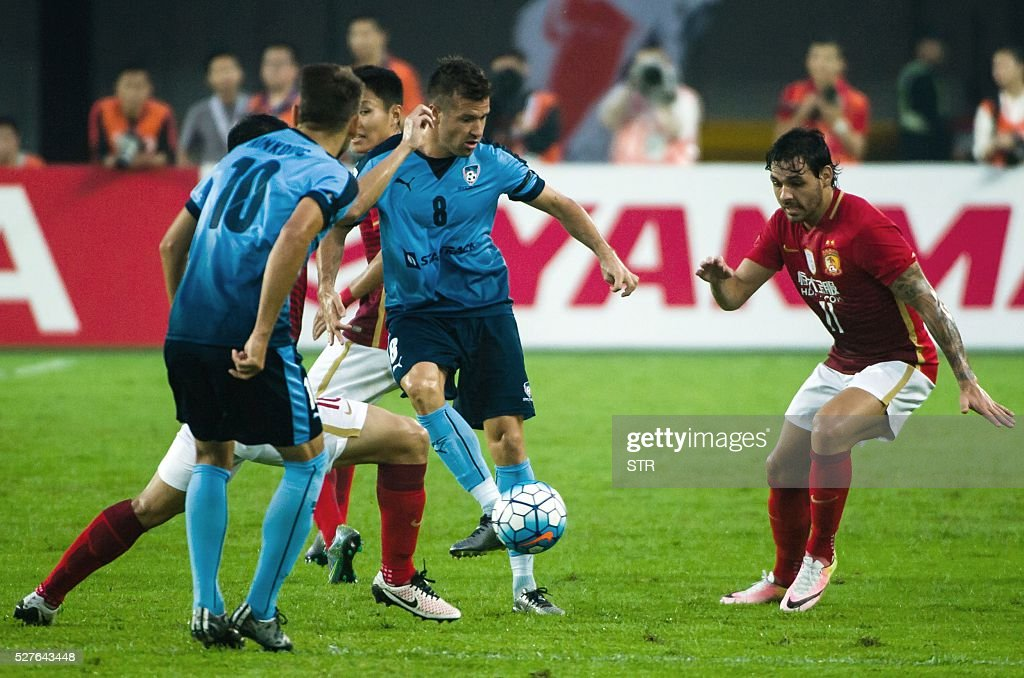 Ricardo Goulart (R) of China's Guangzhou Evergrande fights for the ball with Milos Dimitrijevic (C) of Sydney FC during their AFC Champions League group stage football match in Guangzhou, in China's Guangdong province on May 3, 2016. / AFP / STR