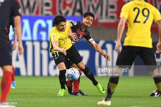 Ricardo Goulart of Guangzhou Evergrande and Mitsuo Ogasawara of Kashima Antlers compete for the ball during the AFC Champions League Round of 16...