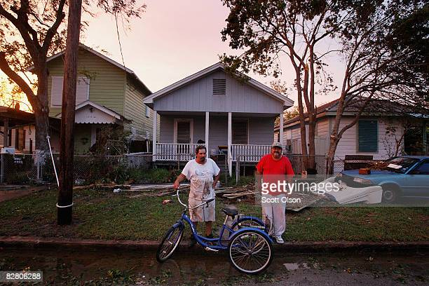 Ricardo Hernandez and Joe Gonzales chat out side Hernandez's flooddamaged home following Hurricane Ike September 13 2008 in Galveston Texas Ike made...
