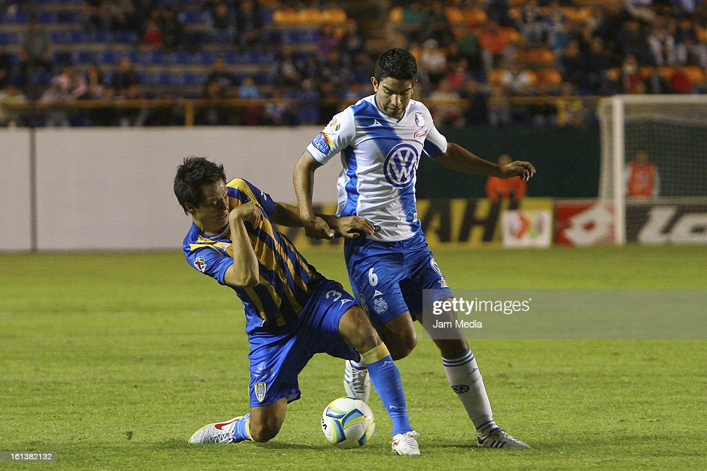 Ricardo Jimenez (R) of San Luis struggles for the ball with <a gi-track='captionPersonalityLinkClicked' href=/galleries/search?phrase=Diego+de+Buen&family=editorial&specificpeople=7624335 ng-click='$event.stopPropagation()'>Diego de Buen</a> (L) of Puebla during a match between San Luis and Puebla as part of the Clausura 2013 Liga MX at Alfonso Lastras Stadium on February 09, 2013 in San Luis Potosi, Mexico.