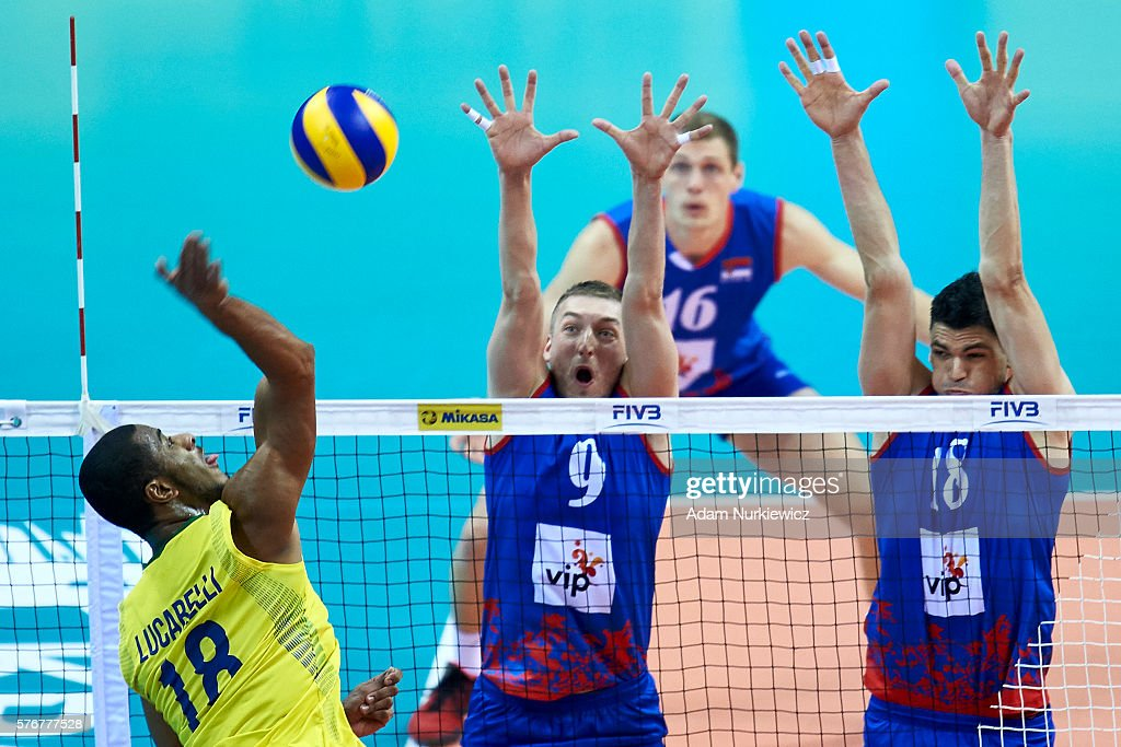 Ricardo Lucarelli Santos De Souza from Brazil attacks against Nikola Jovovic from Serbia and Marko Podrascanin from Serbia while the FIVB World...