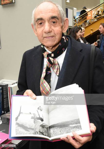 Ricardo Martinez Paz poses with his portrait shot by Catherine Balet incrusted in iconic photo of Robert Capa during Paris Photo 2017 Day Two At Le...