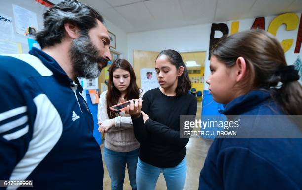 Ricardo Mireles executive director of Academia Avance charter public school speaks with Mr AvelicaGonzalez by cellphone as his daughters Jocelyn...