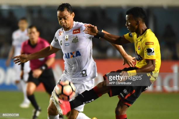 Ricardo Oliveira of Brazils Santos vies for the ball with Dario Aimar of Ecuador's Barcelona during their 2017 Copa Libertadores quarterfinal second...