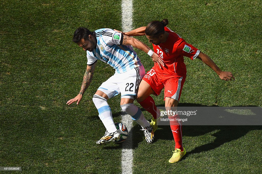Ricardo Rodriguez of Switzerland challenges Ezequiel Lavezzi of Argentina during the 2014 FIFA World Cup Brazil Round of 16 match between Argentina...