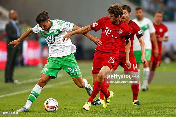 Ricardo Rodriguez of VfL Wolfsburg battles for the ball with Thomas Muller of Bayern Muenchen during the DFL Supercup match between VfL Wolfsburg and...