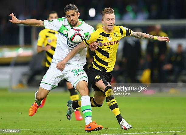 Ricardo Rodriguez of VfL Wolfsburg challenges Marco Reus of Borussia Dortmund during the DFB Cup Final match between Borussia Dortmund and VfL...