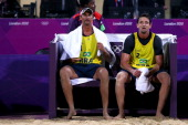 Ricardo Santos and Pedro Cunha of Brazil sit dejected after the lost against Jonas Reckermann and Julius Brink of Germany during the Men's Beach...